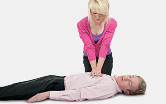 Woman doing chest compressions on male casualty